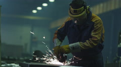 Heavy industry worker at a factory is working with metal on a angle grinder - stock footage