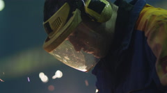 Portrait of a heavy industry worker in a mask that reflects sparks Stock Footage