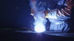 Heavy industry worker at a factory is welding metal in dark interior - stock footage