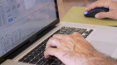 Man working on a laptop computor spread sheet with a keyboard and mouse Stock Footage