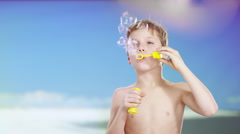 Boy at beach playing with soap bubbles Stock Footage