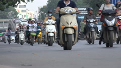 Low angle video of motorbikes riding through the busy business district in Hanoi - stock footage