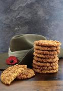 Australian Anzac biscuits with soldier slouch hat on dark vintage background. Stock Photos
