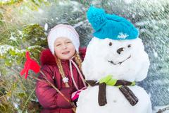 Portrait of a girl with snowman and snow flakes - stock photo