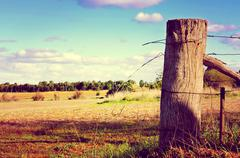 Retro sunset filter style country side scene with old gate post and barb wire - stock photo