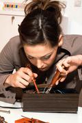 Young woman with fuse-box Stock Photos
