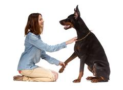 Girl sitting on her knees in front of a large black dog - stock photo