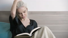 Attractive beautiful girl reading in bed at morning - stock footage