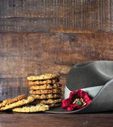 Australian army slouch hat and traditional Anzac biscuits on dark recycled wo Stock Photos