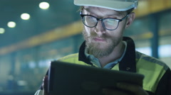 Engineer in hardhat is using a tablet computer in a heavy industry factory - stock footage