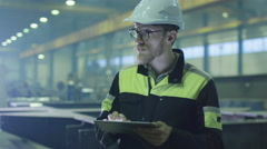 Engineer in hardhat is using a tablet computer in a heavy industry factory Stock Footage