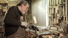 Master goldsmith working with silver in his workshop - stock footage
