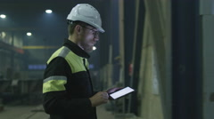 Engineer in hardhat is moving through a heavy industry factory with a tablet - stock footage