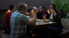 Father, mother, son and daughter eat sushi and rolls with chopsticks - stock footage