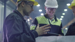 Team of workers at a heavy industry factory have a conversation Stock Footage