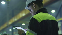 Engineer in hardhat is holding a tablet computer in a heavy industry factory Stock Footage