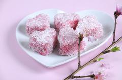 Homemade Australian style pink heart shape small lamington cake on heart shap Stock Photos