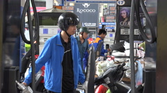 Petrol station, pumping gasoline, motorbikes, Hanoi city, industrial Vietnam Stock Footage