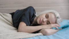 Beautiful Young Blond Woman Waking up and Stretching on the Bed at Home Stock Footage