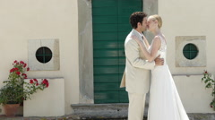 Newlyweds kissing, tilt up to show church with bell Stock Footage