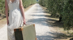 Bride on on rural road with suitcase, rear view Stock Footage