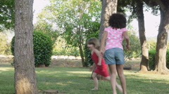 Girl chasing friend around a tree - stock footage