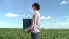 Woman in field with recycling bin full of plastic bottles Stock Footage
