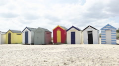 Young couple walking past beach huts Stock Footage