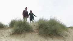 Young couple running over sand dunes Stock Footage