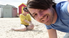 Young couple sitting on beach, looking at camera Stock Footage