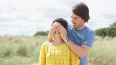 Man covering eyes of girlfriend, then she looks at camera surprised Stock Footage