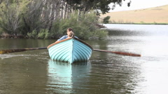 Father and son rowing on lake - stock footage