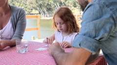 Family playing cards by lake - stock footage