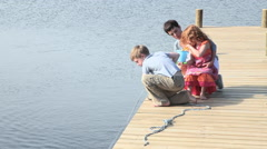 Mother and children sitting on jetty by lake Stock Footage