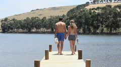 Affectionate couple walking down jetty towards lake Stock Footage
