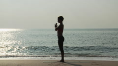 Silhouette of woman by sea in prayer pose Stock Footage
