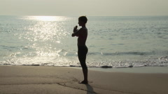 Woman performing sequence of yoga poses by the ocean - stock footage