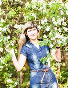 Beautiful spring woman in blooming tree Stock Photos