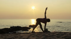Woman practicing yoga on beach at sunset - stock footage