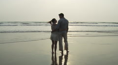 Couple standing in the sea as waves come in - stock footage