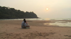 Couple sitting on beach at sunset - stock footage