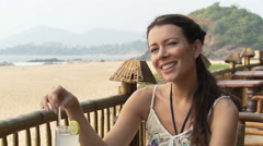 Woman at beach bar, talking to someone who is off camera Stock Footage