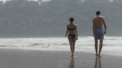 Rear view of couple walking in the sea - stock footage