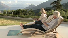 Mature couple on sunloungers looking at view Stock Footage
