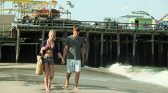 Teenage couple walking hand in hand on beach Stock Footage