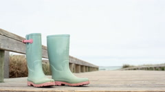 Pair of rubber boots at the coast Stock Footage