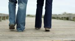 Legs of couple walking on coastal walkway Stock Footage