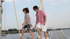 Father and son walking along along yacht deck past sail Stock Footage