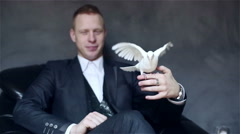 Young attractive illusionist in black suit with white pigeon on his hand. - stock footage
