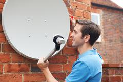 Man Fitting TV Satellite Dish To House Wall - stock photo